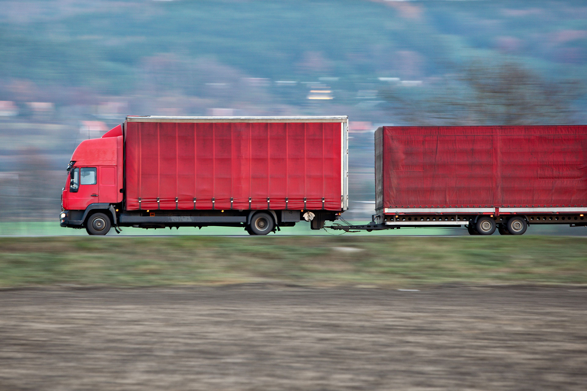 red-camion-truck-goes-fast-on-a-road-panned-image-PUSS5ML